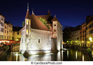 The capital of the Haute-Savoie - Annecy. The main attraction of the city - an ancient fortress-prison on an island in the middle of the river. Fortress beautifully lit and reflected in the dark water.