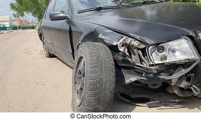 The car after the accident. Broken car on the road. The body of the car is damaged as a result of an accident. High speed head on a car traffic accident.