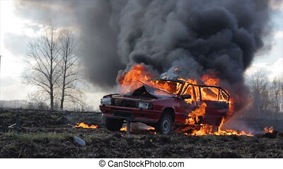 The car burns in the field and its wheel explodes. Car on...