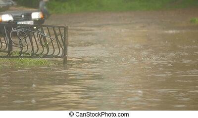 The car drives flooded street during heavy rain - The car...