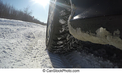 The car goes on the road in winter.