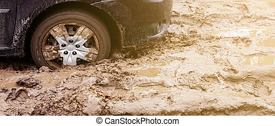 The car got stuck on a dirt road in the mud. Wheel of a car stuck in the mud on the road. Car on a dirt road.