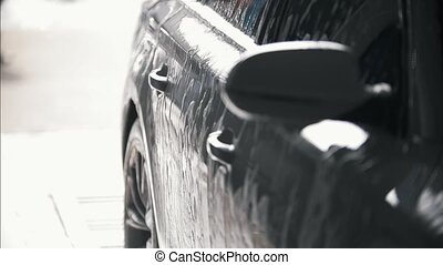 The car is covered by the water after car washing, close up