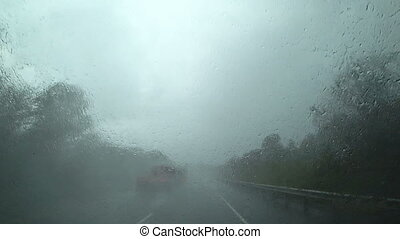 The car is driving in heavy rain on the highway