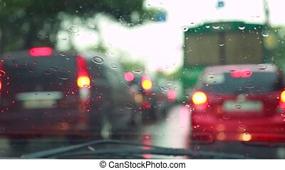 The car is moving around the city, the rain is dripping on the windshield, the wiper blades are working