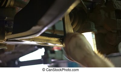 The car mechanic unscrews big car screw with his hand. Auto ...
