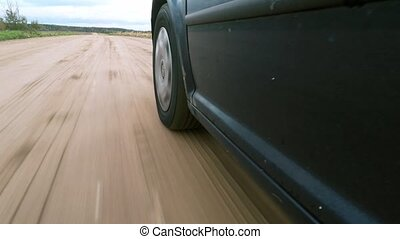 The car moves on a gravel road. - The car moves on a gravel...