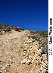 The car on a dirt road on a mountain slope. Greece. Rhodes