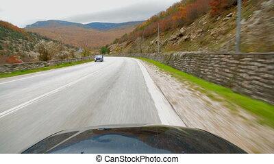 The car rides along a narrow mountain road. - The car rides ...