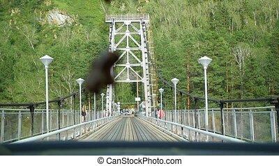 the car rides on a narrow bridge