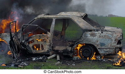 The car was set on fire in a green field, destroyed by a car...