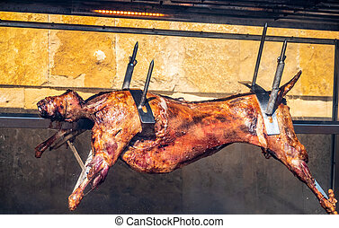 The carcass of a lamb is roasted on a spit.