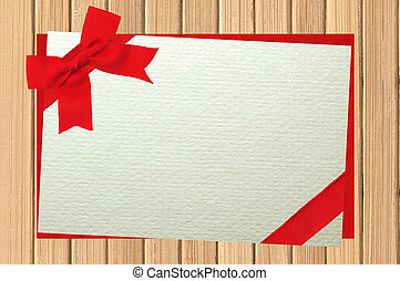 The card decorated with a red bow on envelope on wooden table