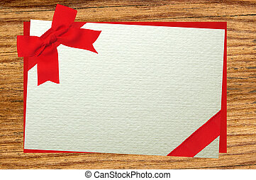 The card decorated with a red bow on envelope over wooden background