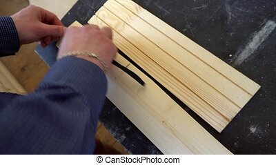 the carpenter measures a piece of Board.