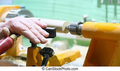 The carpenter's hand processes the wooden part on the...