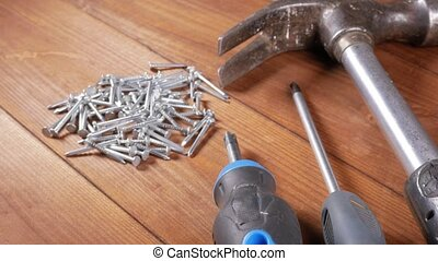 The carpenter's tools lie on a wooden table. Hammer, screwdrivers, nails. The concept of working with wood.