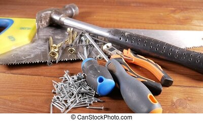 The carpenter's tools lie on a wooden table. Hammer,...