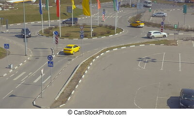 The cars are moving in a circle, in the parking lot next to the shopping center. Multicolored flags in the wind.