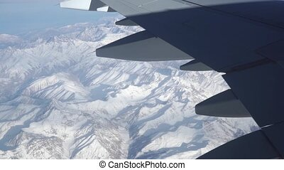 The Caucasus mountains beneath the wing of airliner, aerial view