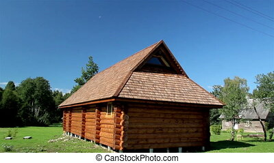 The cedar wooden shingle rooftop of the small log house
