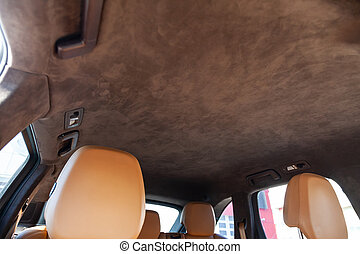 The ceiling of the SUV car pulled by brown soft material alkantara in the workshop for tuning and styling the interior, view from the passanger opened door on central mirror and sun visorson the roof