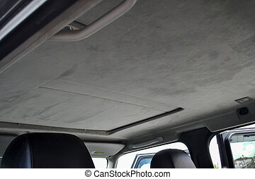 The ceiling of the SUV car with sunroof pulled by gray soft material in the workshop for tuning and styling the interior of the vehicles with sunroof. Auto service industry.
