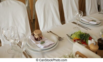 The chairs and table for guests, decorated with candles,...