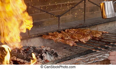The charcoal is being poured with lighting liquid in bbq to...