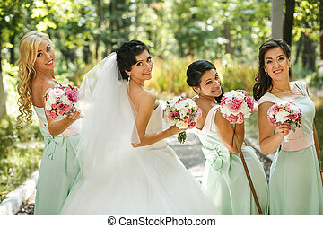 The charming bride and bridesmaids with bouquets