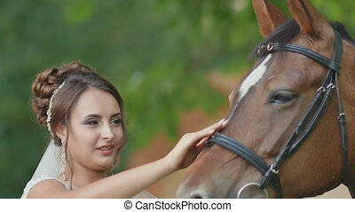 The charming bride gently strokes the horse with her hand. Walking with a horse on your wedding day.