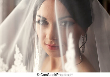 The charming bride is under veil