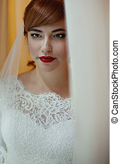 The charming bride looks at window