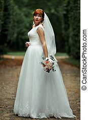 The charming bride stands in the park