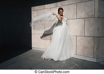 The charming bride stands near wall