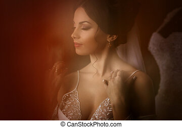 The charming bride stands near wedding dress in the room