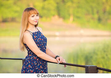 The charming young girl standing on a rustic bridge over the river at dawn sun
