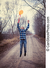 The cheerful boy with a balloon on outdoors