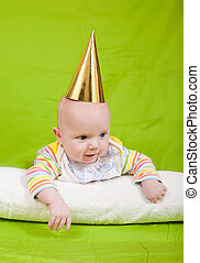 The cheerful kid in a celebratory cap lies on a pillow.