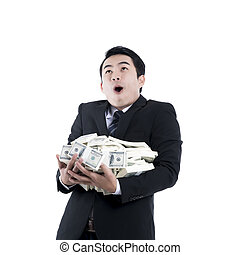 The cheerful young businessman holding a big pile of money in his arms on white background