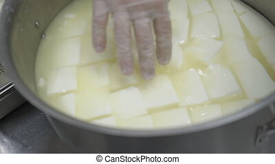 The cheese is being touched by the hand of the worker in the...