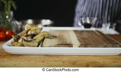 Chef Adds Roasted Mushrooms On A Plate - The Chef Adds...