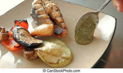The chef adds sauce to a slice of salmon fish, baked vegetables and ribs on a plate in the restaurant. concept of cooking dishes step by step