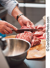 The chef cuts a meat with a knife.