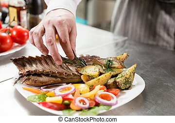 the chef prepares in the restaurant. Grilled rack of lamb with fried potatoes and fresh vegetables. closeup