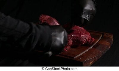 the chef prepares the meat for roasting. butcher's hands cut meat slices with a knife