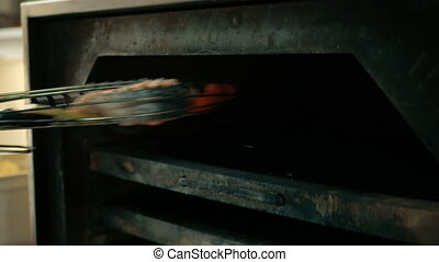 the chef puts a piece of salmon fish, baked vegetables and ribs in the oven in a restaurant. concept of cooking dishes step by step