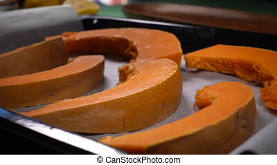 the chef sprinkles pumpkin slices with black pepper, slow...