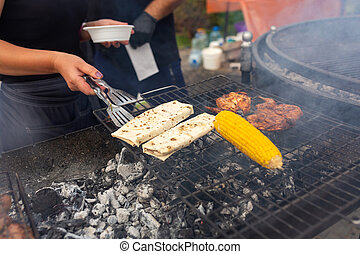 The chef turns over with a spatula two pita breads which are fried on the grill next to corn. Food and cooking equipment at a street food festival