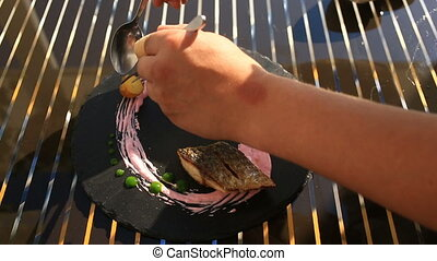 The chief cook decorates a dish of high cuisine with the...